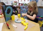 New York School kindergartner Chloe Gulotta, 6, works on a model of a dinosaur in teacher Kim Gamble's classroom.