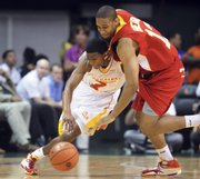 In this April 1 photo, west player Xavier Henry, right, battles for a loose ball against East player Dexter Strickland in the McDonald's All-American Game in Coral Gables, Fla.