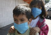 Hiram Diaz, 8, left, gives his 6-year-old sister Adely Diaz a ride on the pegs of his bicycle Saturday while wearing protective masks near the market where their parents own a store in Mexico City. Mexico is struggling with a new strain of swine flu that is showing up in parts of the U.S., including central Kansas.