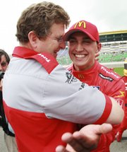 IRL driver Graham Rahal, right, is greeted by crew chief Mitch Davis after qualifying for the Road Runner Turbo Indy 300 auto race at Kansas Speedway on Saturday in Kansas City, Kan. Rahal won the pole with an average speed of 211.311 mph.