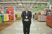 Wal-Mart manager Ryan Edwards stands proudly in the mian aisle of his brand new store just after the grand opening at 7:30 this morning in Lawrence. 