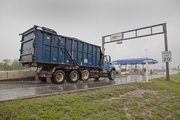 A Lawrence trash truck goes through the K-Tag turnpike toll gate to enter Interstate 70 from North Iowa Street on a Thursday morning in April
