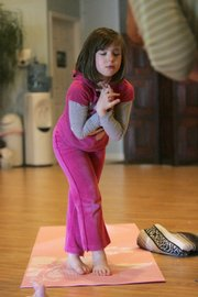 Olivia Kurek, 6, takes part in the Namaste Kids yoga class at The Yoga studio of Shelby in Shelby Township, Mich.