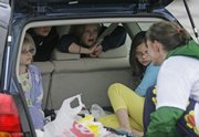 Stacey Wohlford, of Lawrence, greets children in the back of the family vehicle during halftime of a rainy April game at Langston Hughes School. Wohlford recently found her way back to the soccer field after taking 27 years off.