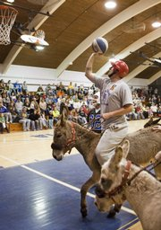"A player prepares to shoot the ball as he guides his mount toward the basket during a donkey basketball event in Moravia, Iowa, in this March 30 photo. Invented in the 1930s, donkey basketball was seen as affordable Depression-era entertainment. The ""sport"" morphed through the years into a popular fundraising vehicle for schools and other organizations. But animal rights groups contend the donkeys are mistreated by participants and handlers."