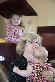 Brenda Childers holds her 4-month-old granddaughter Patricia Cooper, while her other granddaughter Marguerite Cooper, 5, plays in the background at Childer's house Thursday, May 7, 2009. Childers daughter and the girls mother Patricia Cooper has gained a new appreciation for her mother since becoming a mom to her two young girls.