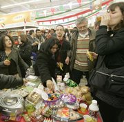 Shoppers help themselves to food during a protest organized by an anti-capitalist group that staged a free-for-all picnic March 28 inside a supermarket in Saint Ouen, northwest of Paris. The protesters fill up tables inside the supermarket with store goods and then encourage others in the store to join them, not paying for the items taken. This is part of a string of symbolic protests to nibble away the markets' profits at a time when many consumer pocketbooks are pinched by economic crisis.
