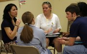 Topeka Correctional Facility inmate Michelle Eicher, center back, discusses a reintegration project with Baker University students Iliana Krehbiel, left, and Michael Weaver in this April 23 file photo at the Topeka Correctional Facility.