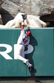 Los Angeles center fielder Torii Hunter makes a catch to save a home run on a ball hit by Kansas City's Miguel Olivo in the ninth inning. The catch helped the Angels beat the Royals, 4-3, on Sunday in Anaheim, Calif.