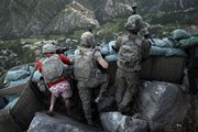 Soldiers from the U.S. Army First Battalion, 26th Infantry, take defensive positions at firebase Restrepo after receiving fire from Taliban positions Monday in the Korengal Valley of Afghanistan's Kunar Province. Spc. Zachery Boyd of Fort Worth, Texas, far left, was wearing 'I love NY' boxer shorts after rushing from his sleeping quarters to join his fellow platoon members. With him are Jordan Custer of Spokane, Wash., center, and Spc. Cecil Montgomery, of Louisiana.