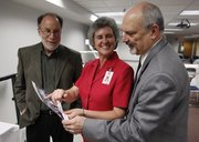 Retiring employees from the Lawrence school district, from left, Bruce Passman, deputy superintendent; Mary Rodriguez, chief operations officer; and Superintendent Randy Weseman attend a reception in their honor Wednesday at district headquarters, 110 McDonald Drive. They looked at a district photograph taken about 30 years ago and laughed at the hairstyles in vogue at the time.