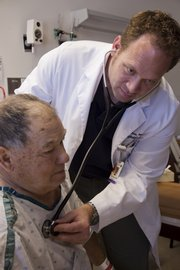 Matt Harms, a hospitalist at Lawrence Memorial Hospital, checks the heartbeat of patient Kenneth Bryant from Eudora.