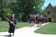 Karen Exon, Baker University faculty member, leads the processional in front of the Osborne Chapel as it moves across Baker's campus Sunday before the commencement ceremony.