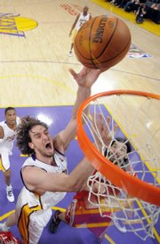 Los Angeles Lakers center Pau Gasol, left, puts up a shot in front of Houston Rockets forward Luis Scola. The Lakers won, 89-70, Sunday in Los Angeles.