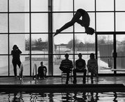 A large window provides a bright backdrop to silhouette a diver and judges during a swim meet.