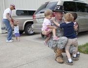 Pat Stuber, a KU graduate and currently an army captain with the Tennessee Army National Guard, greets three of his children Thursday at the hangar of his father Al Stuber, far left, at the Lawrence Municipal Airport. Stuber is preparing for his fourth deployment which could be Iraq or Afghanistan. It will be his first deployment since his children, two sets of twins, were born. Hugging Stuber from left are Elaine, 22-months and Ben and Nick, 3. At left with Stuber's father Al, of Lawrence, is his 22-month-old daughter Alida.