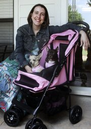 Melissa Garcia and her two dogs, Daisy Mae, left, and Isabella, show off Garcia's stroller and dog outfits obtained for great deals Monday at her home in Edmond, Okla. Garcia pens consumerqueen. com, a blog read by at least 30,000 people each month and by corporate America.