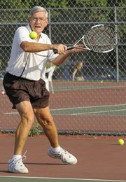 George Morton, Leavenworth, returns a serve in the Lawrence Open Tennis Tournament Friday night at the Lawrence Tennis Center.