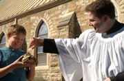 Ian Babcock, Lawrence, holds out his leopard tortoise named Deronimus for a blessing with holy water by the Rev. Jonathon Jensen during a past St. Francis of Assisi blessing of the animals at Trinity Episcopal Church, 1011 Vt., in this 2002 file photo. The annual event at Trinity is one way Jensen has performed outreach with the Lawrence community during his tenure.