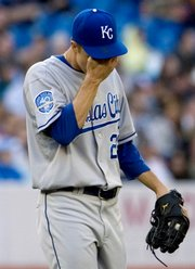 Kansas City pitcher Zack Greinke wipes his brow during the fourth inning where he gave up four runs to the Toronto Blue Jays. The Royals lost, 9-3, Friday in Toronto.