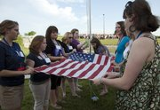Young women attending Sunflower Girls State are in town for a week's worth of government and politics activities. A group of assistant counselors retired the flag outside the Dole Institute of Politics on Kansas University's West Campus on Sunday evening.