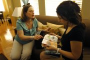 Melanie Lyke, left, discusses Avon products with her client, Jennifer Jarnagin, right, May 15 in Jarnagin's home in Franklin, Tenn. Lyke sells Avon products as a way to earn a second income.