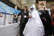 An Iranian groom talks with his bride as they arrive Friday at a polling station to vote for the presidential elections in downtown Tehran, Iran. Iranians packed polling stations from boutique-lined streets in north Tehran to conservative bastions in the countryside Friday.