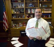 In this Feb. 14, 2008 file photo, Secretary of State Ron Thornburgh holds copies of voter registration applications in Topeka, Kan. Thornburgh ended his bid to be the next Kansas governor Monday, saying he lacked the funding and support to challenge for the Republican nomination.