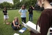 "Members of the Lawrence Youth Ensemble prepare to rehearse a scene from ""Home on the Road"" last week in Watson Park. From left are Natasha Hurt, 12, ensemble co-director Rachael Perry, Anna Taylor, 14, Rob Parker-Ortley, 16, and Emily Reno, 14. The nine-member ensemble wrote the play, a series of vignettes about Lawrence, and will perform it three times this weekend."