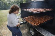 Bev Herrman checks on chicken wings and riblets in the smoker, which can cook nearly 500 pounds of meat.