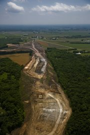 An aerial view of the U.S. Highway 59 realignment project 1 mile south of Pleasant Grove Hill shows the vast clearing efforts to accommodate eventual construction of a new four-lane freeway. Plenty of work remains, as crews still need to blast through limestone underneath to help improve site distances for drivers when the road opens in late 2012.