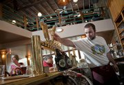Bartender Jon Bunch pours two growlers of beer as patrons eat and drink at Free State Brewing Co., 636 Mass. Proprietor Chuck Magerl says an integral part to restaurant success is reliable staff.