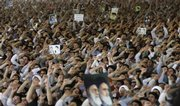 Holding posters of the late Iranian spiritual leader Ayatollah Khomeini and supreme leader Ayatollah Ali Khamenei, worshippers chant slogans during Friday prayers at the Tehran University campus in Tehran, Iran.