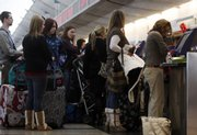 In this Dec. 21, 2008, file photo, travelers queue up at a ticketing counter at Denver International Airport. United Airlines has recently started charging passengers an extra $5 if you pay a $15 baggage charge at the airport instead of online.