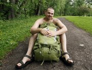 Andrew Williams poses without his shirt behind his backpack Thursday at a park near his home in Warren, Pa. Williams plans to participate Sunday in Naked Hiking Day, an annual event celebrated on the first day of summer by a relatively few enthusiasts. 