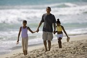 In this Aug. 12, 2008, file photo, then Democratic presidential candidate Sen. Barack Obama, D-Ill. walks down Kailua Beach in Kailua, Hawaii, with his daughters Malia, 10, left, and Sasha, 7, during their vacation in Hawaii. President Obama spoke Friday at the White House about being a father, imploring dads everywhere to be involved in the lives of their own children.