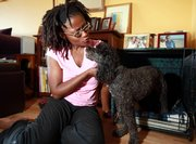 "Susan Jacobs, cosmetics consultant and freelance journalist, and Kingston, her 4-year-old poodle mix, share a moment Saturday at what Jacobs describes as Kingston's ""condo within a condo"" at her home in Long Beach, Calif."