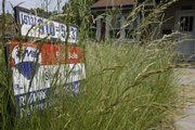 A lawn is overgrown around a for sale sign posted outside a vacant house for sale June 4 in Cincinnati. Sales of previously occupied homes fell 8.5 percent in the Midwest from April to May.