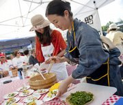 Yasuko Takatori, front, and Satoko Miyoshi set out samples of chirashi sushi prepared with locally grown vegetables and a few ingredients from Japan during a cooking demonstration at the Farmer's Market on Saturday. Both women are visiting from Japan with the exchange group, Global Partners for Local Organic Foods, that is in Lawrence to learn about sustainable agriculture.