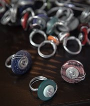 Michelle Merritt makes homemade rings out of old buttons that she is selling to raise money for an international adoption.