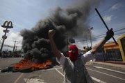 Supporters of Honduran President Manuel Zelaya demonstrate in front of a tire bonfire Sunday in Tegucigalpa, Honduras. Soldiers arrested Zelaya and disarmed his security guards after surrounding his residence before dawn Sunday, his private secretary said. Protesters called it a coup and flocked to the presidential palace as local news media reported that Zelaya was sent into exile.