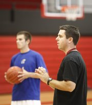 New Lawrence High head basketball coach Mike Lewis instructs his players during summer workouts Wednesday, July 1, 2009 in the LHS gymnasium. In back is LHS senior Drake DeBiasse.