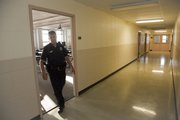 Officer James Druen walks around empty classrooms in Fraser Hall during an evening check on campus. During the summer months, the campus is less populated, and officers will check out rooms that are not locked.
