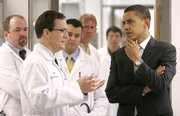 President Obama talks with Dr. Mark Anderson while touring a cardiology research lab before speaking about his health care plan at the University of Iowa in Iowa City, Iowa. A new book documents the legacy of other presidents' attempts at introducing health care legislation.