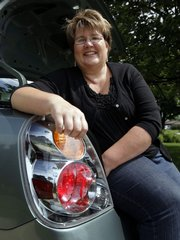 Real estate agent Laura Musall shows the new taillight on her 2004 Nissan Altima at her home in Fishers, Ind., in this June 22 photo. Musall's taillight burned out and her husband thought he could make a quick repair by replacing the bulb. He couldn't easily remove the plastic light cover, so he ended up prying it off with a screw driver, shattering it in the process. The replacement was $250 from the dealer. Many car owners who try to save money by doing their own repairs find that it costs more in the end after a botched attempt.