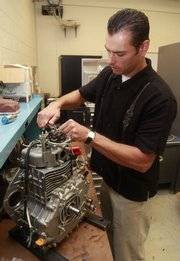 Chris Depcik, an assistant professor of mechanical engineering, works on a motor for an experimental car at Kansas University's Learned Hall.