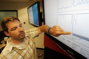 Shawn White, Director of External Operations for mobile and Web site monitoring company Keynote Systems, points Wednesday to a graph of the Department of Defense Web site performance, top graph, and availability, lower graph, at the company's headquarters in San Mateo, Calif.  This graph shows very poor availability and performance of the DOD Web site on Monday.