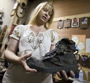Connie Ernatt holds a boot worn by Wichita Police Lt. John Galvin of the department's Explosives Ordnance Unit in Wichita. He was injured and later died in 2000 when fireworks he was loading into a detonation pit for a training exercise ignited prematurely. Ernatt is making castings of Wichita police officers' boots and shoes for the Law Enforcement Memorial that will be outside Wichita City Hall.