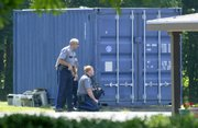Lawrence police take up a position behind a storage container Thursday at the Jayhawk Motel, 1004 North 2nd Street. Up to 10 law enforcement officers had surrounded a room at the motel and had it under observation for over an hour before a man was taken under arrest.