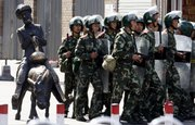 Chinese paramilitary police patrol near a sculpture of a Uighur on a donkey Saturday in Urumqi, China.